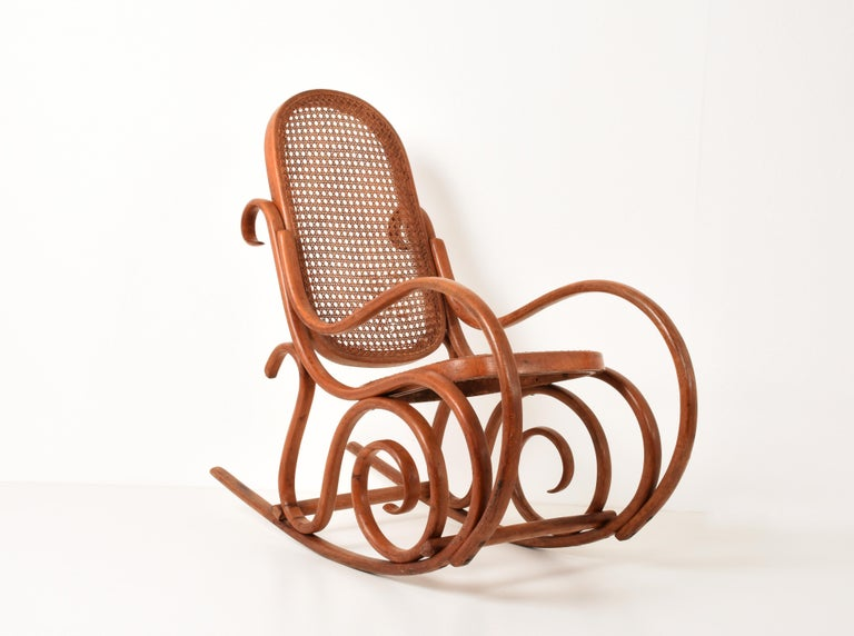 Thonet. A vintage bentwood child's rocking chair with cane back and seat, 1930s.