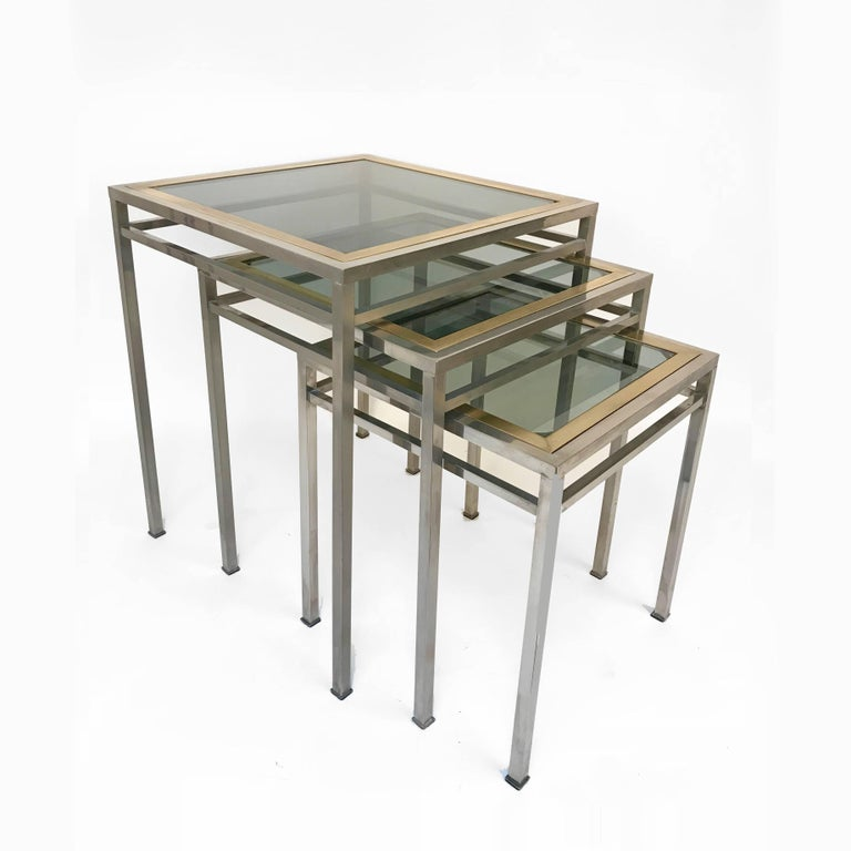 Three wonderful nesting tables in brass and crystal glass. They were produced in Italy during the 1970s.  These three tables are an iconic example of Mid-Century Modern lines and material, with the perfect integration of the smoked glass with