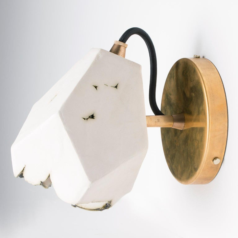 This sculptural wall sconce features a clean geometric shape and a unique textural matte finish. The shade is handcrafted from slabs of unglazed white porcelain with highly individual black oxide burnout detailing at the edges. The unfinished brass