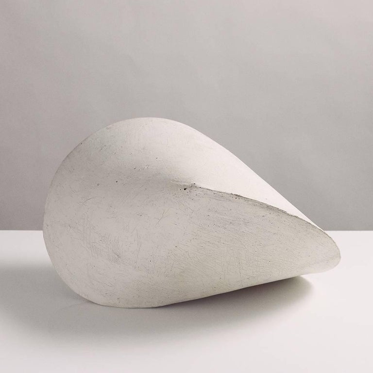 This large stoneware ceramic pod sculpture is both geometric and organic, reminiscent of a perfect seashell. Each pod is hand-built from flat slabs of earthy beige stoneware, then treated with a fine wash of white porcelain, giving it a delicate