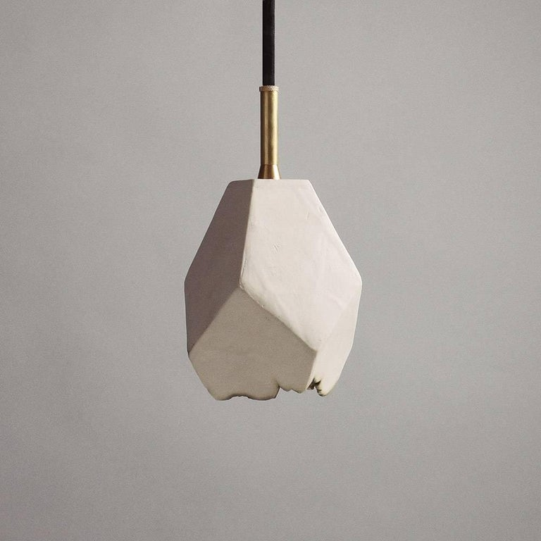 This sculptural pendant lamp features a clean geometric shape and a unique textural matte finish. The shade is handcrafted from slabs of unglazed white porcelain with highly individual black oxide burnout detailing at the edges. An unfinished brass