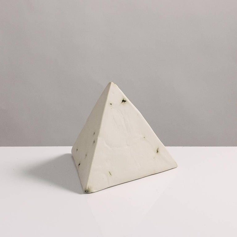 This sculptural geometric tetrahedron is handcrafted from slabs of unglazed white porcelain with highly individual black oxide burnout detailing, giving each of its four sides a unique textural matte finish. The organic texture contrasts with the