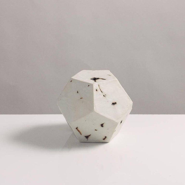 This sculptural geometric dodecahedron is handcrafted from slabs of unglazed white porcelain with highly individual black oxide burnout detailing, giving each of its 12 sides a unique textural matte finish. The organic texture contrasts with the