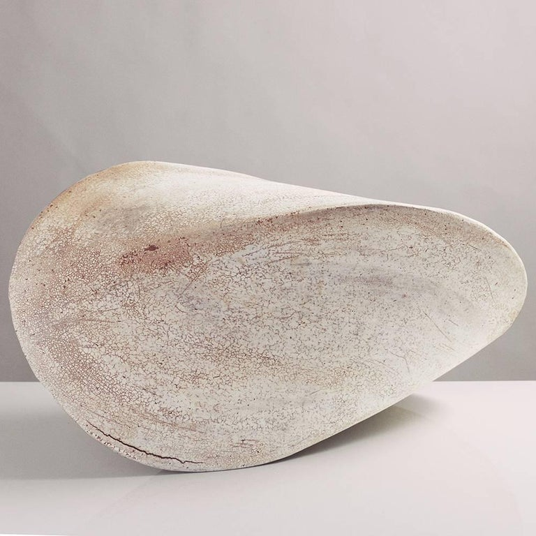 This massive stoneware ceramic pod sculpture is both geometric and organic, reminiscent of a perfect seashell. Each pod is hand-built from flat slabs of earthy beige stoneware, then treated with a fine wash of white porcelain, giving it a delicate