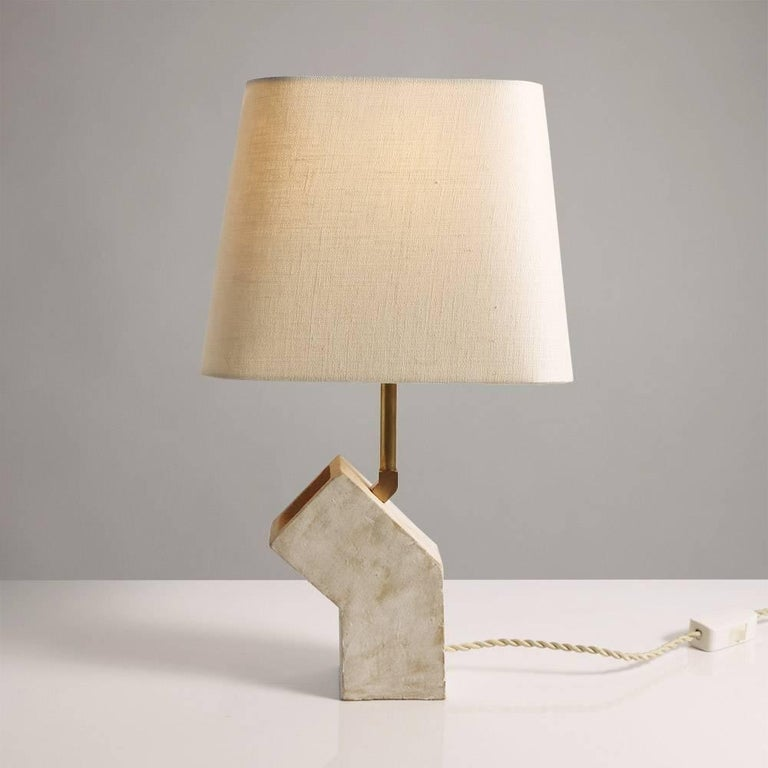 Inspired by midcentury Brutalist architecture and building materials, this small table lamp balances a strong substantial ceramic base with delicate brass hardware and a rounded geometric beige linen shade. Perfectly sized for a bedside table. The
