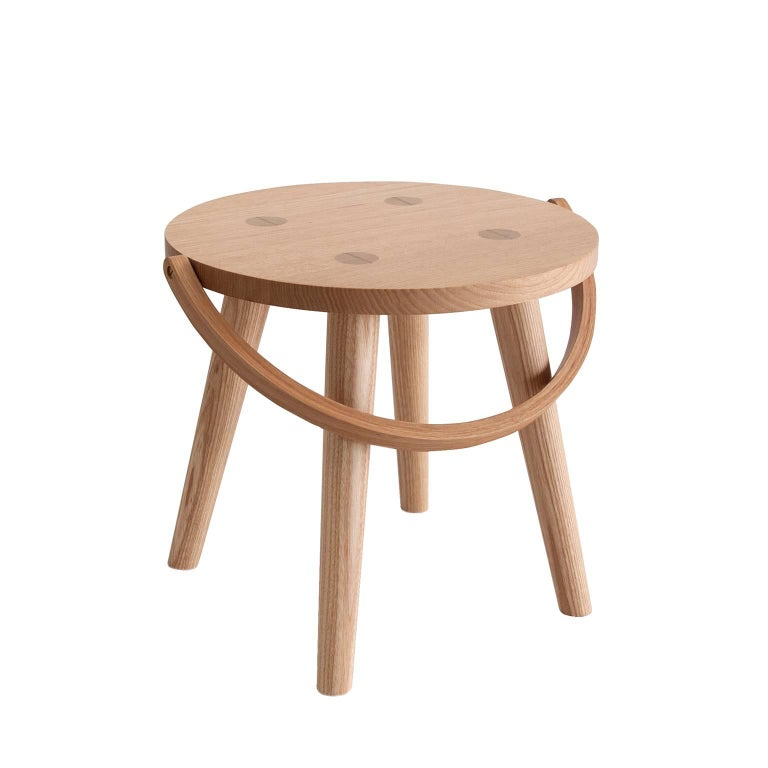 The Step Bucket Stool is a single sized, low seat, or step stool, and the smallest of four versions from the Bucket Stool Collection, a family of solid ash furniture featuring bentwood handles. These versatile pieces can function as either a seat or