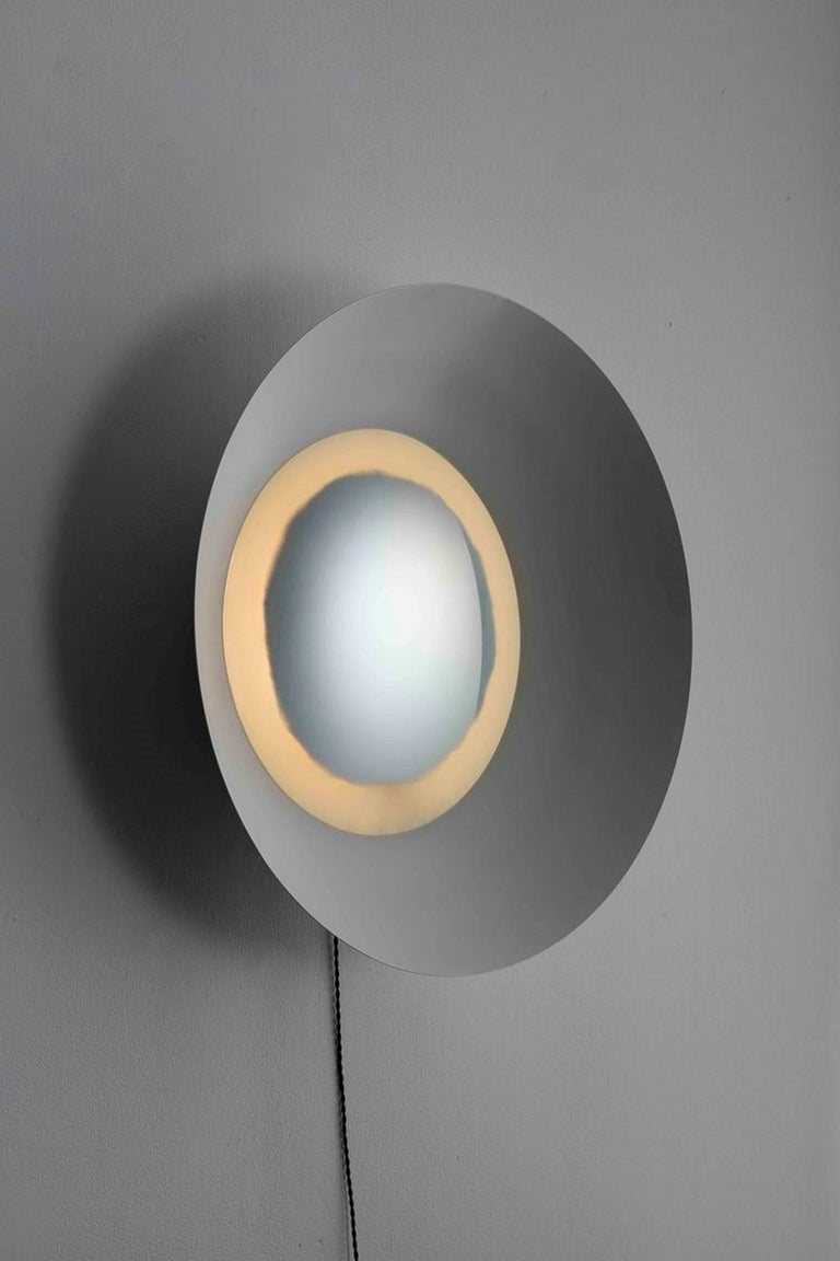 This curved light fixture creates a stunning lighting effect using various curved surfaces. The body of the light is a formed hemisphere with an inset convex mirror. The mirror is backlit around the perimeter through an area with distressed texture