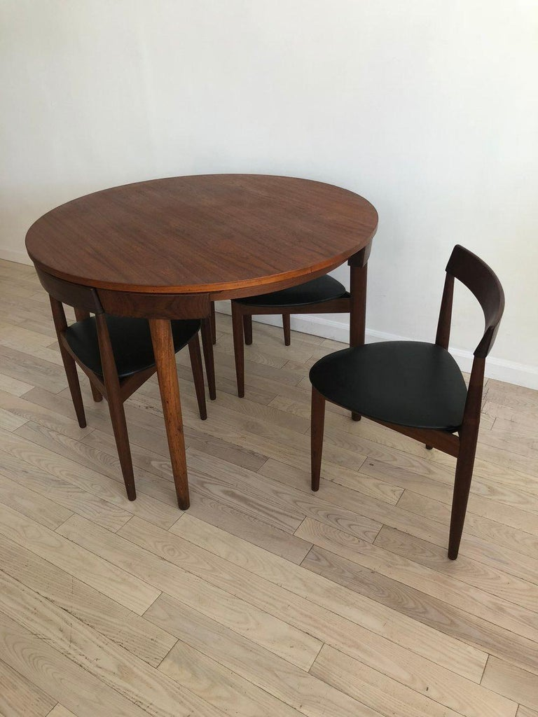 Midcentury Danish Hans Olsen for Frem Rojle teak dining table set. Four chairs that fit into the round dining table. The dining chairs are three-legged. Super rare and beautiful set of furniture. Minor break in one top section of leg that has been
