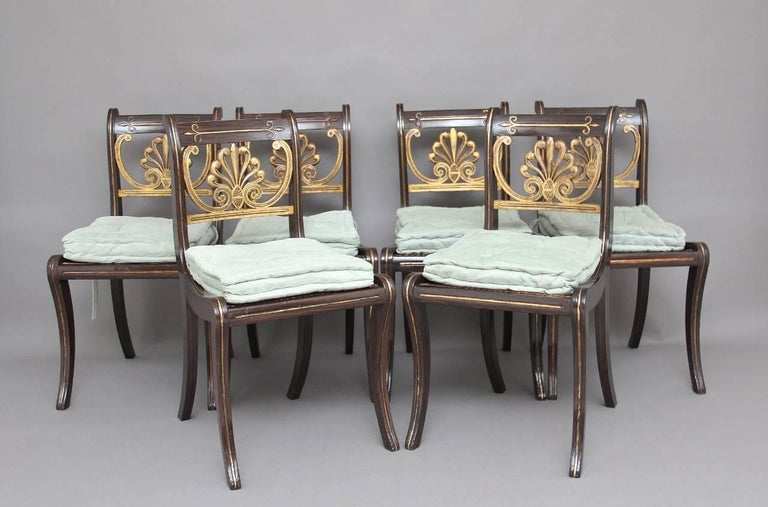 A set of six 19th century simulated rosewood and gilt sabre leg dining chairs, the top and side rails having gilt inlay with the centre rail decorated with a gilt ornate flower pattern, the chairs having a cane seat with a drop in fabric cushion,