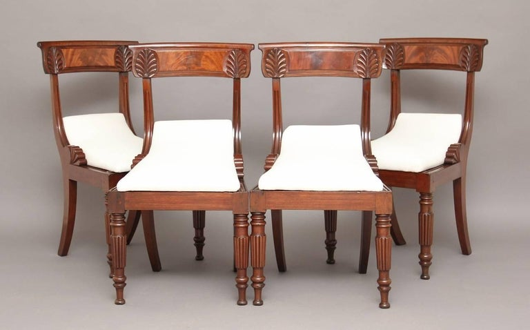 A set of four mahogany dining chairs with carved back rail upholstered in a calico seat with turned front legs and swept back rear legs.