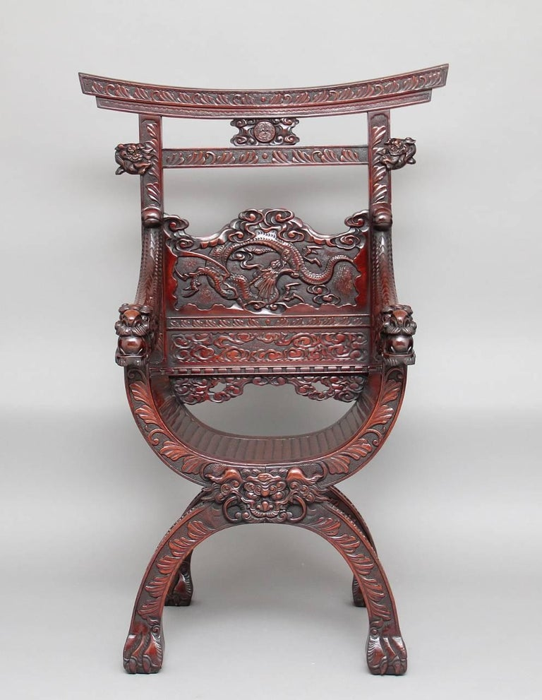 19th century Chinese throne / armchair profusely carved all-over, the back panel decorated with a carved dragon and carved fret work below, with carved dragon arms united onto a curved seat, supported on a cross frame base standing on paw feet,