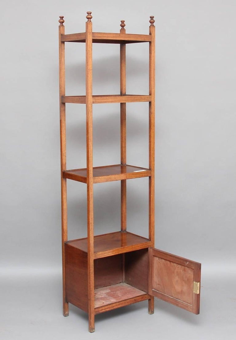 Early 19th century mahogany four-tier whatnot with fluted square columns, the top section with turned finials, the bottom section having a cupboard with a lockable single door, circa 1810.