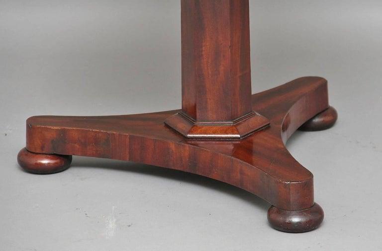 19th century mahogany three tier metamorphic circular dumbwaiter with a triangular platform base terminating on bun feet, circa 1830.