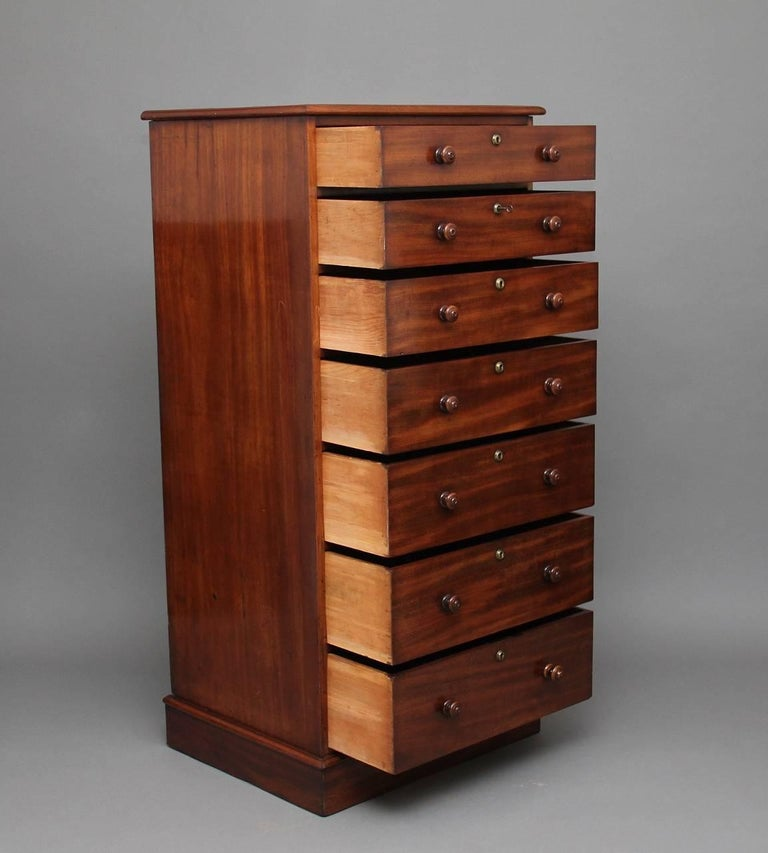 A tall 19th century mahogany chest in excellent condition, with a moulded edge top, with seven graduated drawers with original turned wooden knobs, standing on a plinth base, circa 1840.