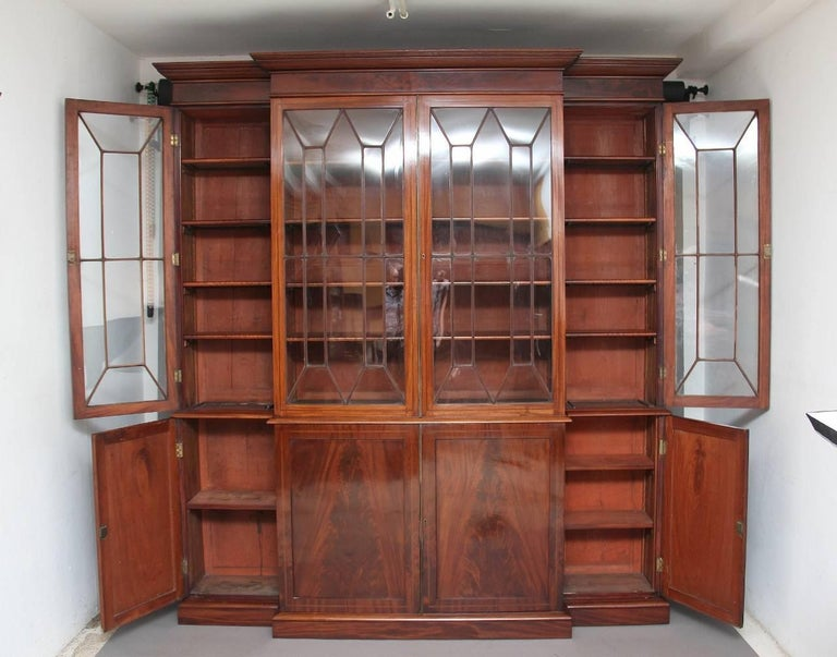 19th century four door mahogany breakfront bookcase, the moulded cornice above four astragal glazed doors opening to reveal four adjustable shelves in each section, the bottom section having four cupboards with flame mahogany panel doors, the