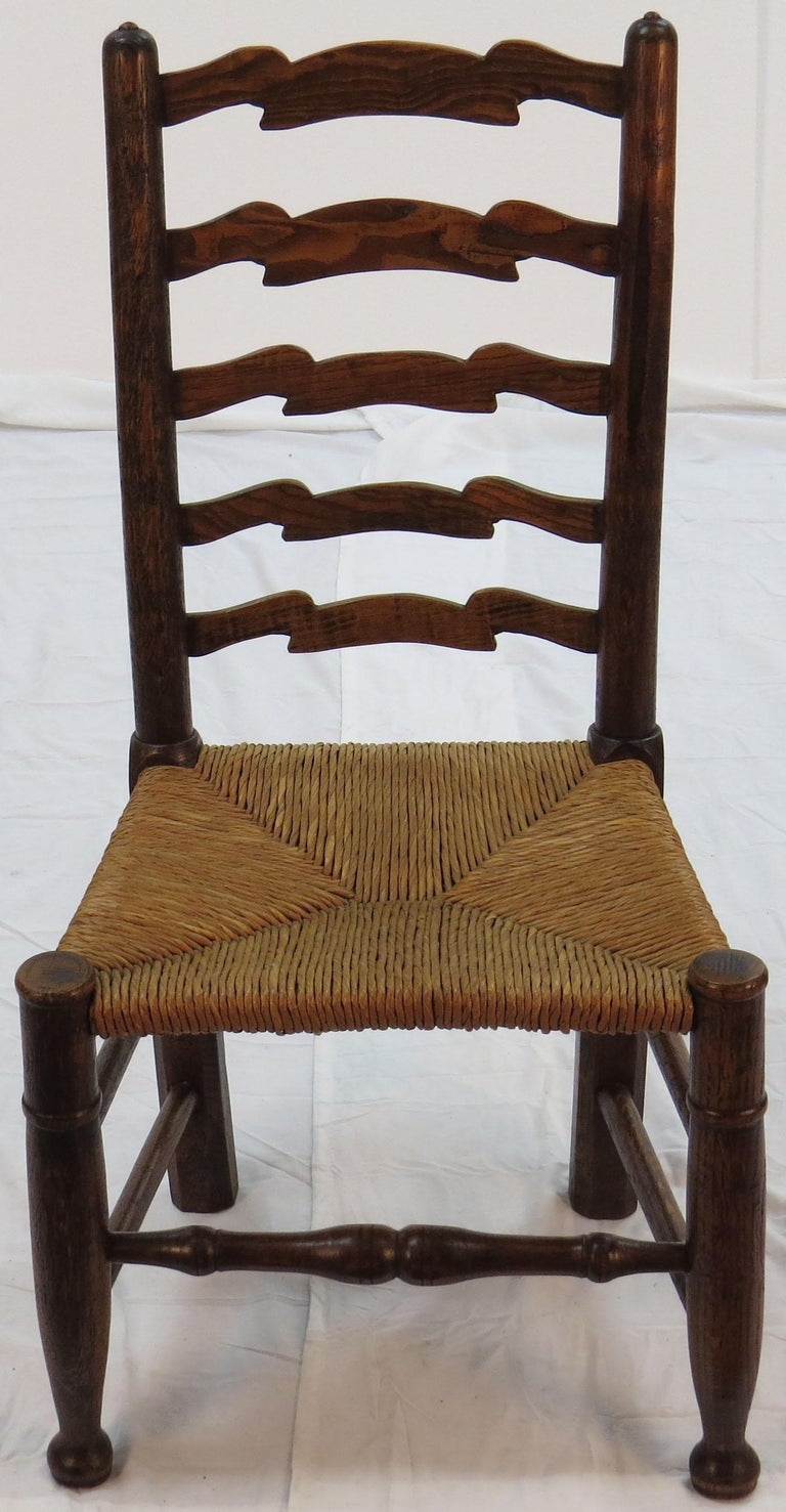 This stunning set of antique ladder back dining chairs were made of solid oak in England, circa 1940. That date technically makes them vintage rather than antique. The set consists of six chairs, none of which have arm rests.
