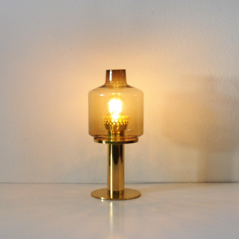 Hans-Agne Jakobsson brass and glass table lamp model B-102 with brass and handblown amber color glass shade supported by a polished brass base. This model B-102 table lamp was designed by Hans Agne Jakobsson in the 1960s, and produced by his own