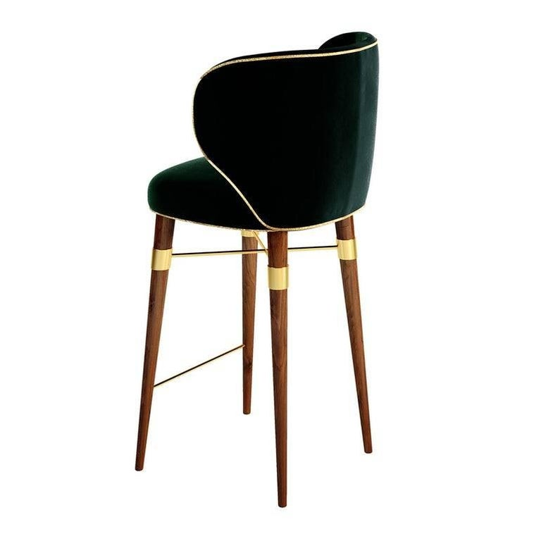 Upholstered in velvet or leather, a Classic design radiates from this chair's modern lines. The Langston bar chair features solid walnut legs with brass accents.
