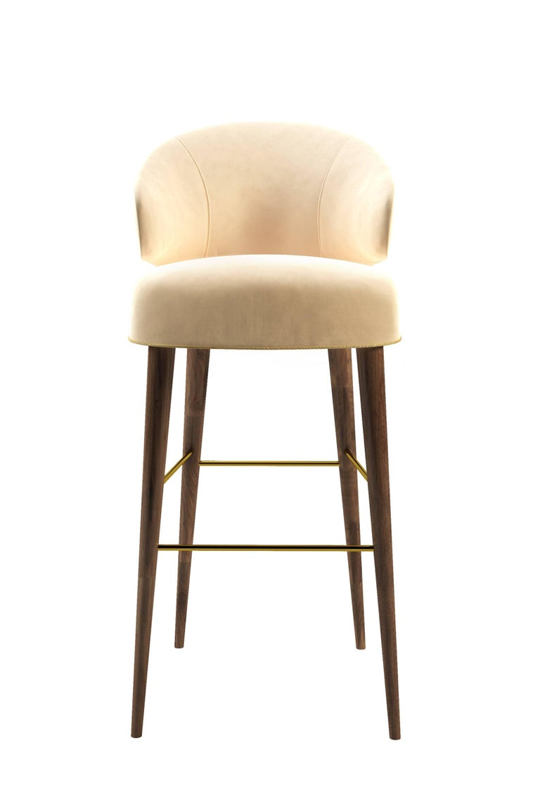 The Myla bar chair features a classic design with bright cotton velvet, contrasting piping and brass accents.   Standard fabric options are velvet and leather. COM available. Metal details options are polished and brushed brass, polished and brushed