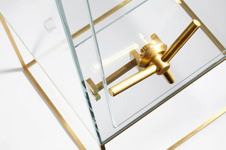 Storage furniture in transparent extra-light crystal with mechanism and base in brushed brass. 