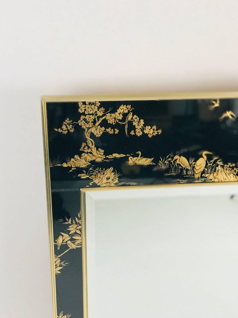 Large black and gold Labarge chinoiserie mirror. Made of brass and glass, the mirror has églomisé chinoiserie in black and gold. 