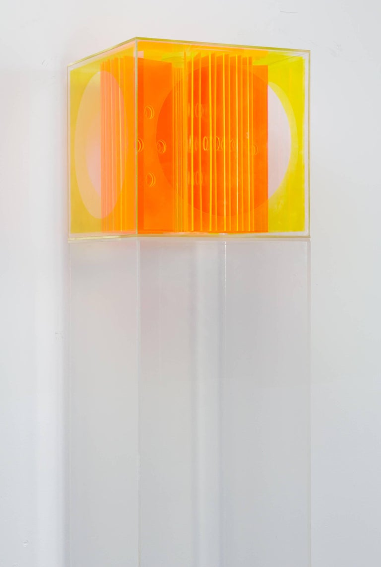 Bright acrylic Op-Art cube sculpture with perforated orange panels and yellow walls, set atop an acrylic pedestal.