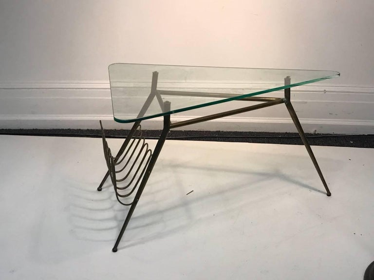 Modernist Italian brass tripod tapered leg base table with triangular glass top and angled brass magazine rack. Designed in The 1950s in Italy.