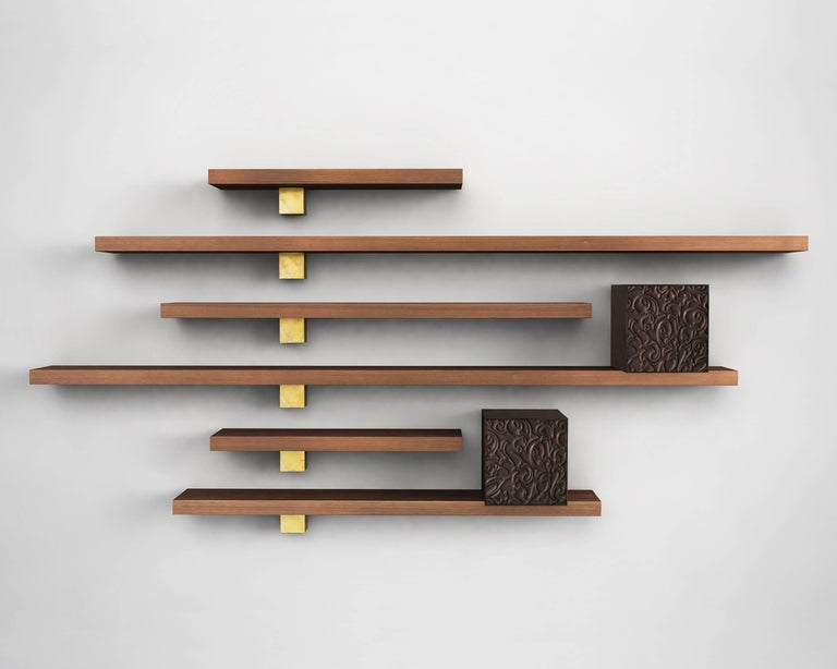 The delicate pattern of carvings, the precious grain of the solid walnut and the brightness of the brass castings give rhythm to wall the pieces are on, creating sophisticated solutions, for preserving and exhibiting. 