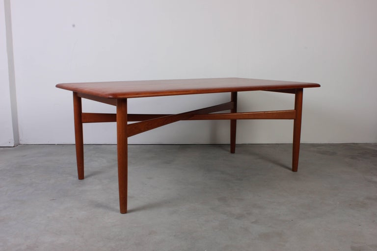 This midcentury Danish coffee table is made out of solid teak of high quality. The tabletop in very good condition and the table also has crossbars between the legs as a nice detail.