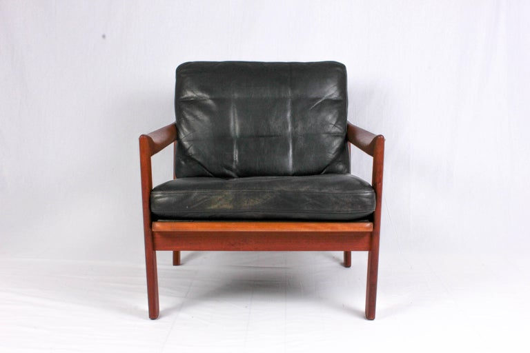 This midcentury teak armchair is designed by Danish designer Illum Wikkelsø and produced by Niels Eilersen. The chair has beautiful twisted armrests and leather upholstery with minor signs of usage and patina. A very decorative and comfortable chair