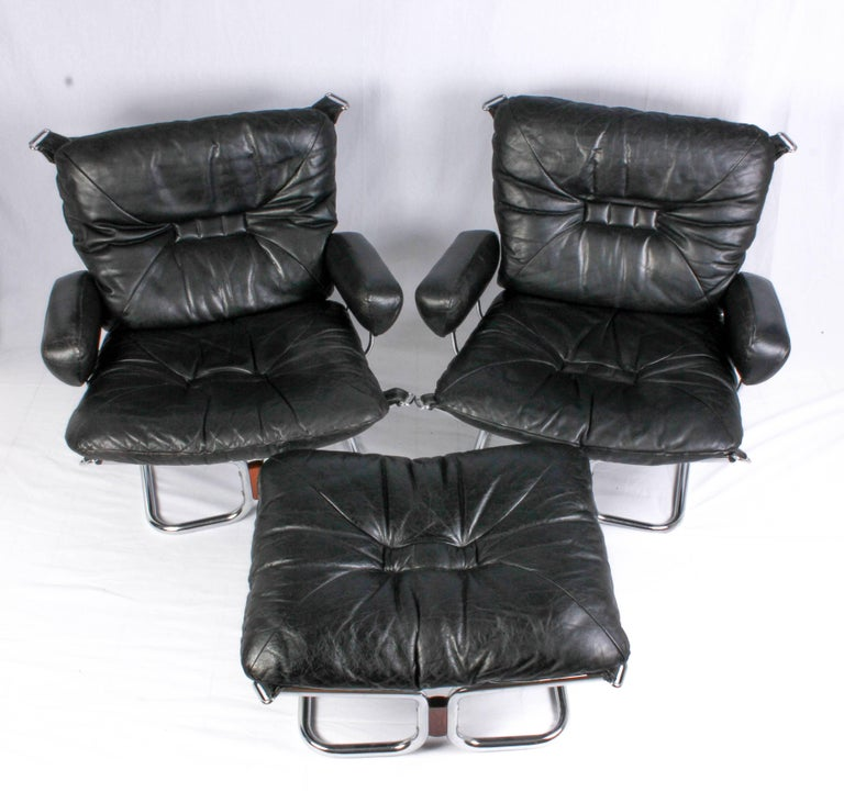 A pair of lounge chairs and a ottoman designed by Norwegian designer Ingmar Relling. The chairs and ottoman are made of a chrome frame, leather cushions and rosewood details. They are all in excellent vintage condition with minor signs of