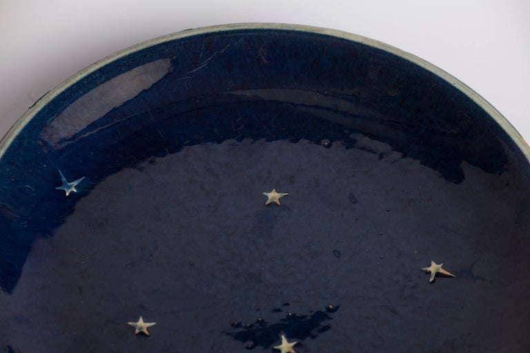 A ceramic enameled plate with stars. On the back of the plate there's number: 614 A Measures: Diameter 28 cm Height 3.5 cm.
