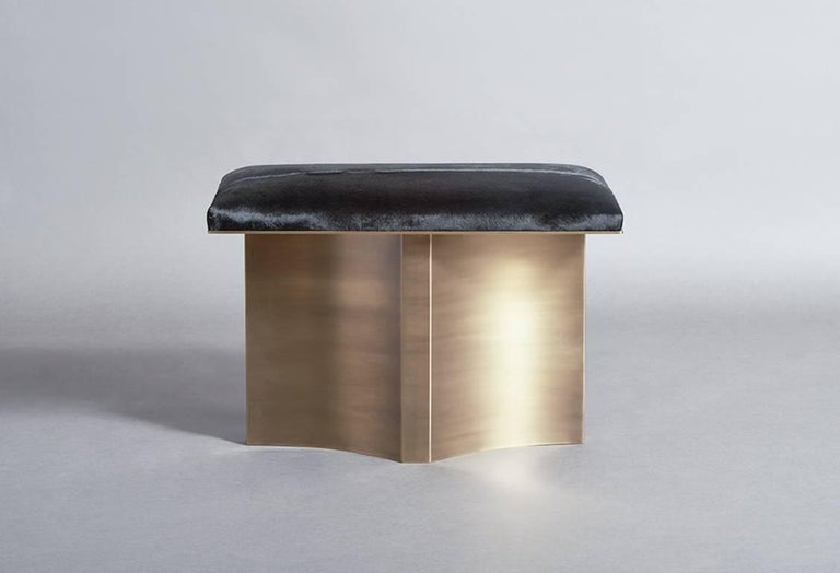 V brass bench with black hair on hide cushion with linear aged brass base transforms the everyday bench into a luxurious objet d'art.  Customization available. Please inquire for additional information.  Featured in Elle Decor.   Designed and