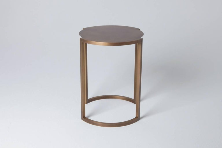 Solid arched brass legs outline the delicate aged brass top of the Covet end table, creating a balance of precision and elegance.  Also, available in bronzed black steel as pictured.  Designed and hand crafted  by Soraya Osorio.