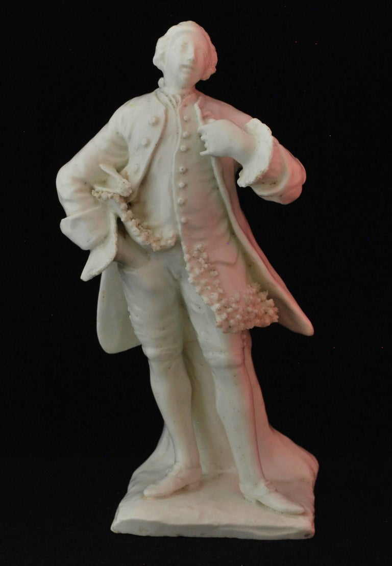 In the white. David Garrick, modelled in a theatrical pose against a tree stump. He wears a tied wig, knee breeches above stockings with incised clocks and buckled shoes; an open, long tailed coat above a waistcoat with lace-edged tails, a simple