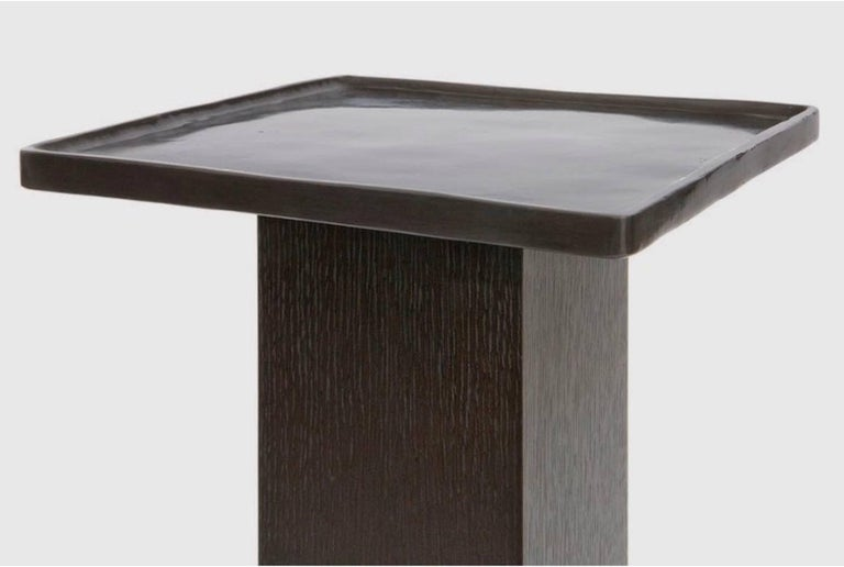 The sturdy rift-sawn oak pedestal supports a functional cast-bronze tray finished with an antiqued patina in this stylish yet sensible accent table. Use it in a living room to display decorative items such as sculptures or busts and plant-filled