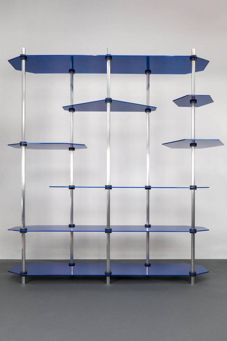 Modular shelving or storage unit with adjustable height shelves and customizable shapes and colors. For use as a bookshelf or display shelving or entertainment / media centre. Custom color options are available. Shown in a metallic blue glaze with
