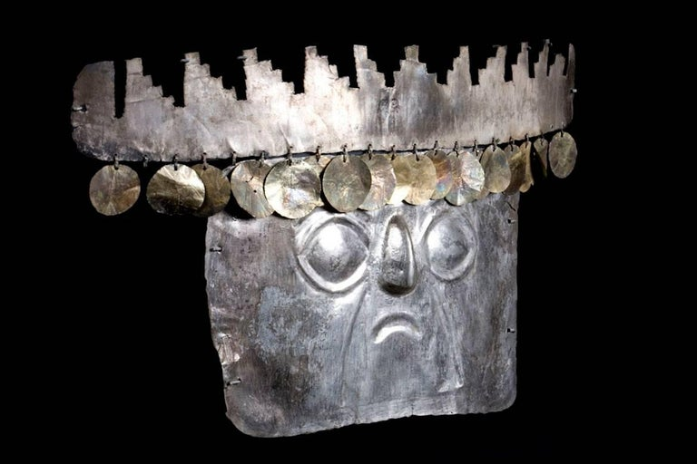 A rare, sheet silver human face mask with simple relief facial features including large, almond shaped eyes and downturned mouth. Classic stepped pyramid headdress with round, very thin sheet gold sequin adornments. Perforated along the edges for
