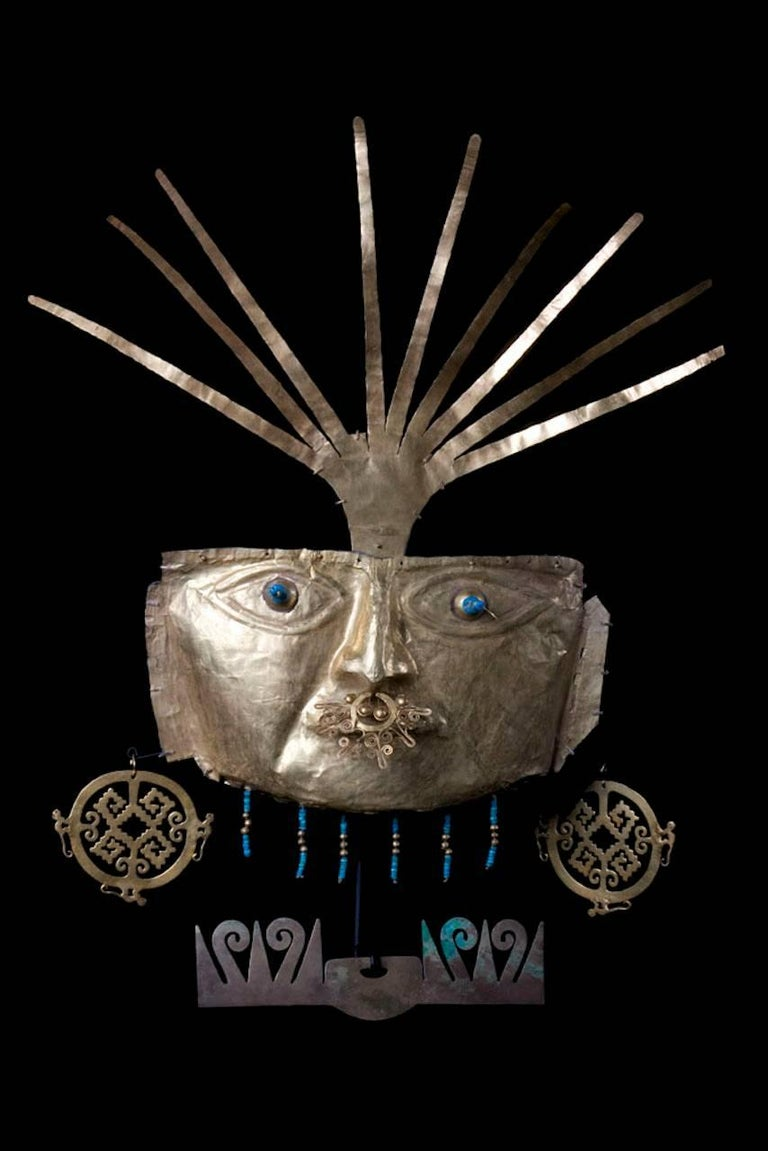 A high karat heavy sheet gold human face mask with large almond-shaped eyes and recessed pierced pupils. Multiple small perforations along the upper and lower edges for attachment. Left ear somewhat detached, overall surface crinkles and creases,