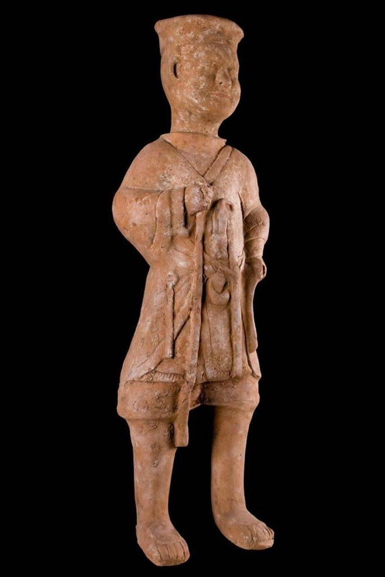 Huge hollow molded terracotta, standing male figure wearing a hip-length multi-layered robe with a collared neck. Implements suspended from his waist, holding a staff in his right hand and wearing a disc type cap. Some earthen encrustation on