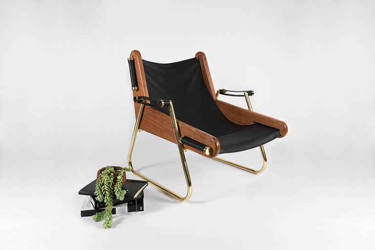 Form meets function in this sleek yet extremely comfortable suspended leather sling chaise. All materials are sourced locally specifically for each piece and handcrafted. Mexican walnut hardwood, double thickness bovine leather and varnished brass.
