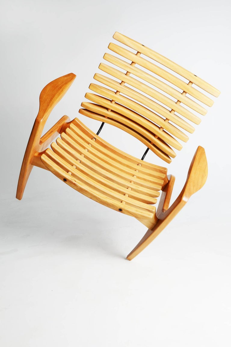 This sculptural chair designed by Brazilian designer Henrique Canelas consists of a structure in solid wood with ribbed seat and backrest,  manufactured with fine woodworking techniques that don't require the use of nails and screws. Carbon steel