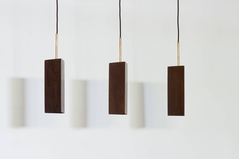 This pendant lamp is made in Brazilian Canela Preta reclaimed dark wood and brass.  Different types of wood available upon request. Ready for E27 lamps.