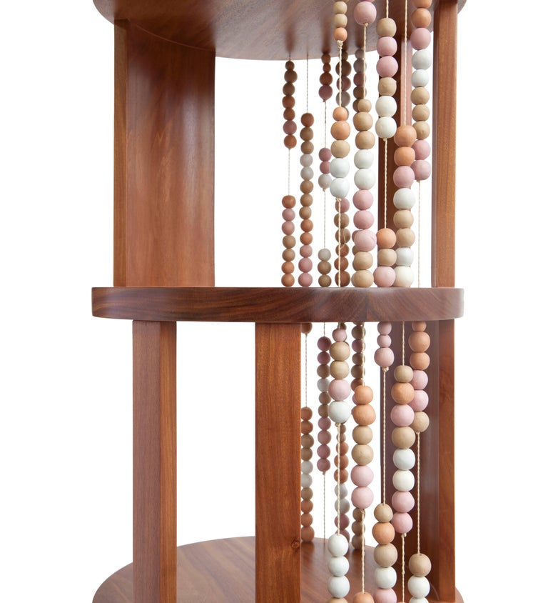 All the levels of this round bookcase, made of cabreuva hardwood, are permeated by buriti palms yarns with ceramic beads, creating different compositions depending on the angle we look at. All the soft colored shades of the ceramic come from the