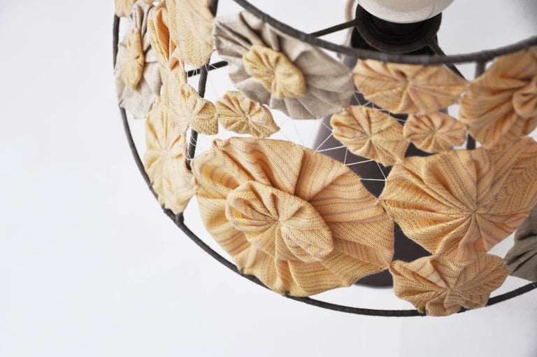 The base of the Luminaire is made of Ipê solid wood turned. The shade, that has its structure coated with naturally dyed cotton threads, receives handmade embroideries (fuxicos) made with fabrics weaved in manual looms.   The cotton thread had its