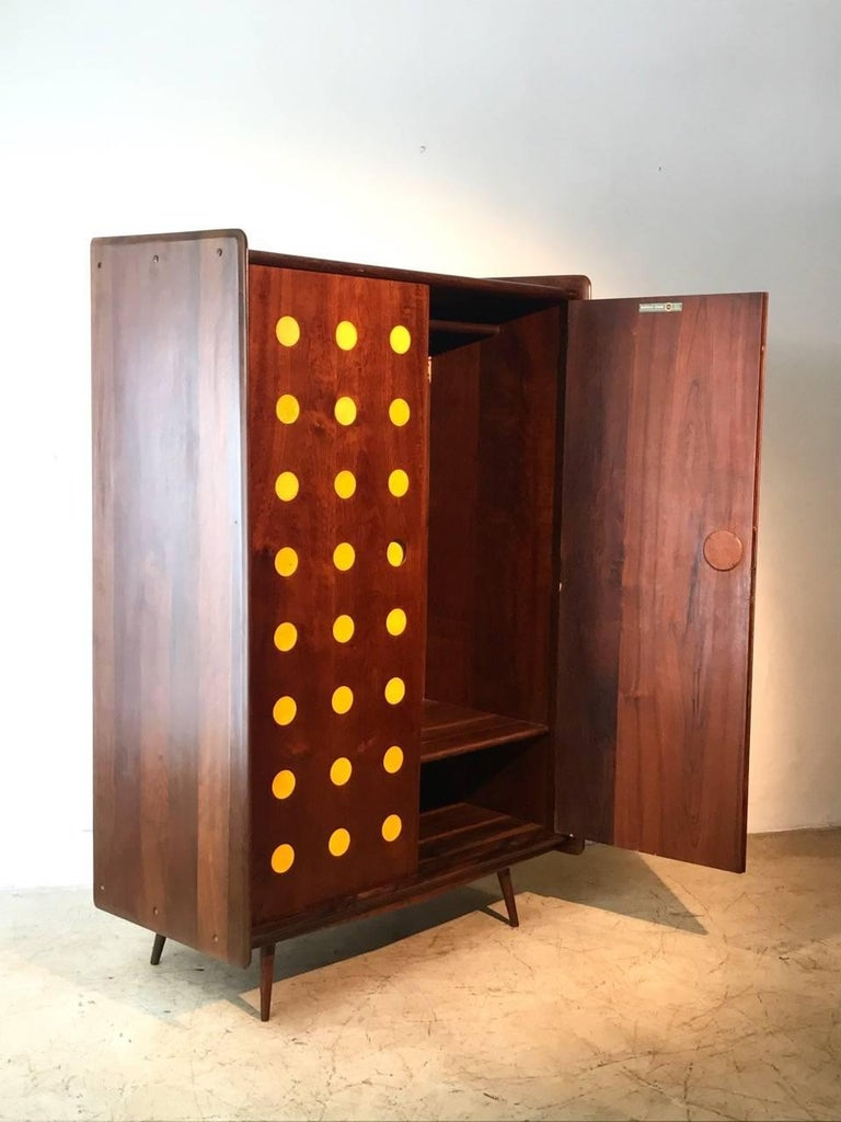 Midcentury armoire or clothes-press made of solid imbuia wood and yellow details. This is an important piece of the modern Brazilian furniture made by Cimo that was furniture maker specialized in office furniture, they made only a few home furniture