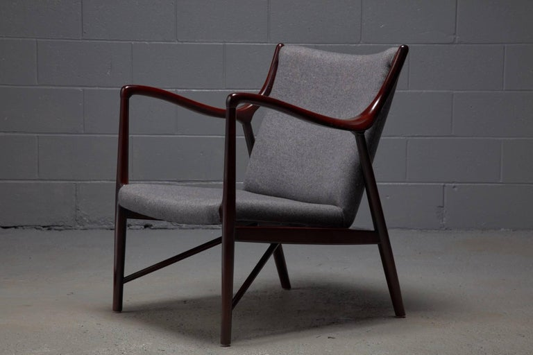 Designed in 1945 by Finn Juhl for a collaboration with Niels Vodder, the NV45 armchair is an iconic design. This armchair being offered is in the style of this widely sought after chair and features a polished rosewood-colored wood frame and grey