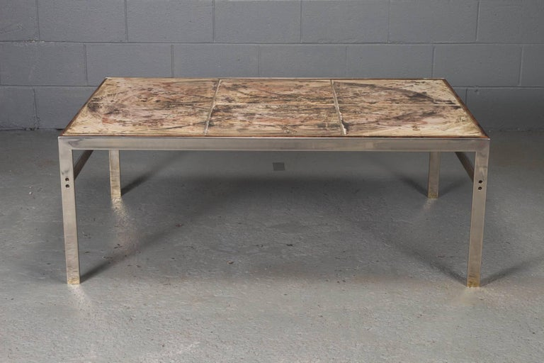 This coffee table is made of hand-painted tile with a rosewood and chrome frame. The piece features a signature indicating it was created in 1973.