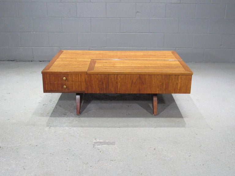 This coffee table by George Nakashima for Widdicomb was designed in 1961 for the Origins Line. Featuring two drawers, storage compartment with lid on top, and open storage in the back. Label in drawer and burn stamp signature on bottom. Laurel wood