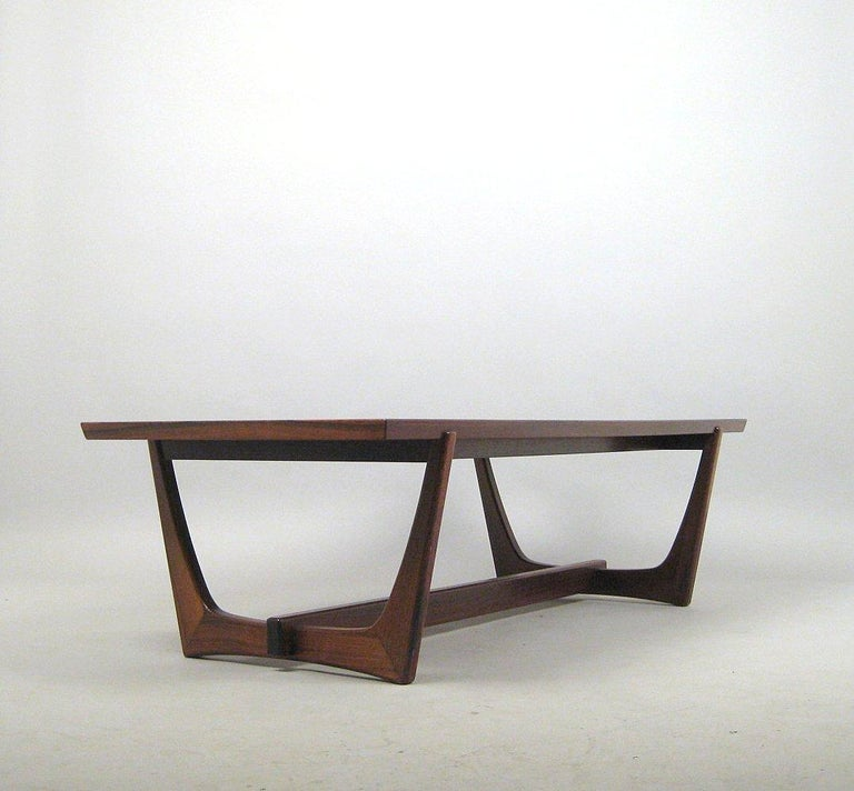 Danish designed or manufactured rosewood coffee table with bent frame legs that replicate the rib structure of a ship's hull. Construction with frame in solid, dark wood with a strong grain, veneered top.